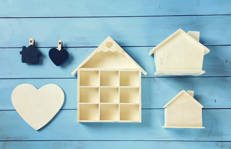 wooden toy: Set of various wooden houses on blue wooden background, top view image. vintage filtered Stock Photo