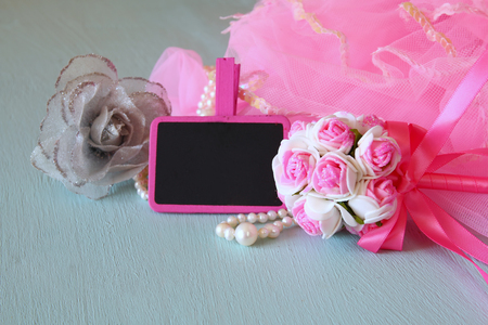 party outfit: Small girls party outfit: pearls and wand flowers next to small empty chalkboard on wooden table. bridesmaid or fairy costume Stock Photo