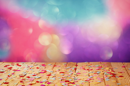 pink party whistle on wooden table with colorful confetti. vintage filtered image Stock Photo
