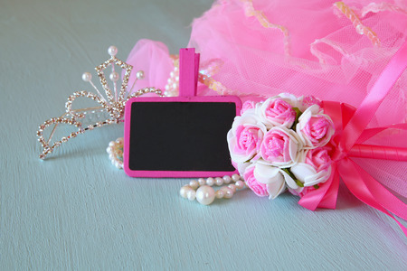 party outfit: Small girls party outfit: crown and wand flowers next to small empty chalkboard on wooden table. bridesmaid or fairy costume Stock Photo