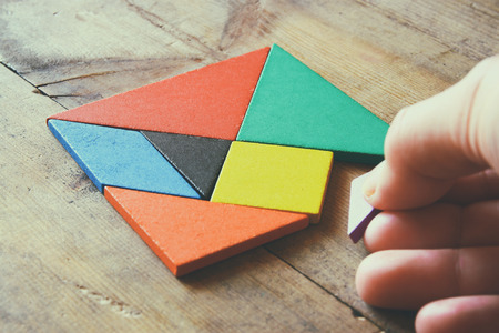 mans hand holding a missing piece in a square tangram puzzle, over wooden table.