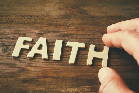 word: man hand spelling the word FAITH from wooden letters, retro style image