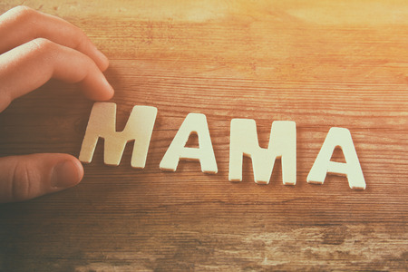 word MAMA made with block wooden letters on wooden background. vintage filtered and toned