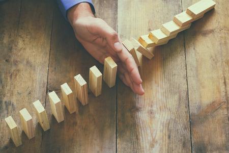 derrumbe: vista desde arriba de la mano masculina la colocación de bloques de madera en una torre. alisado y el concepto de estrategia. vendimia filtrada Foto de archivo