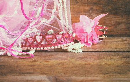 party outfit: Small girls party outfit: crown and vail on wooden table. bridesmaid or fairy costume. vintage filtered