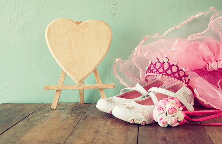 girl shoes: Small girls party outfit: white shoes, crown and wand flowers on wooden table. bridesmaid or fairy costume. vintage filtered