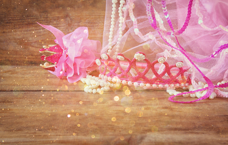 party outfit: Small girls party outfit: crown and vail on wooden table. bridesmaid or fairy costume. vintage filtered with glitter overlay Stock Photo