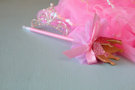 party outfit: Small girls party outfit: crown and wand on wooden table. bridesmaid or fairy costume