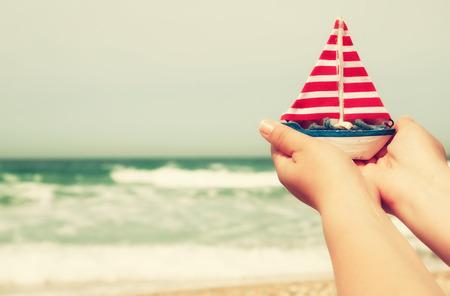vacaciones en la playa: manos de la mujer que sostienen un barco delante de horizonte de mar
