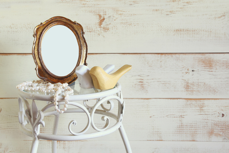 neckless: Antique blank vintage style frame, white pearls and couple of wooden birds on elegant table. template, ready to put photography