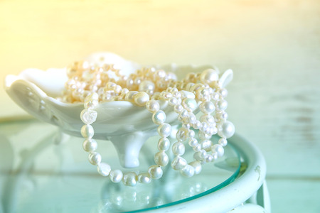 perl: high key image of white pearls necklace on vintage table. selective focus Stock Photo
