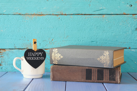phrase novel: cup of coffee with a little heart shape chalkboard with the phrase: HAPPY WEEKEND next to stack of old books. Stock Photo