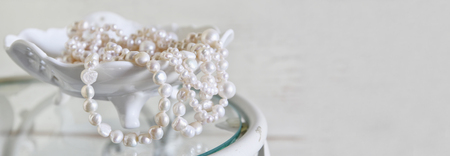 perl: website banner background of white pearls necklace on vintage table. selective focus Stock Photo