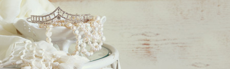 website banner background of white pearls necklace and diamond tiara on vintage table. toned image. selective focus Stockfoto