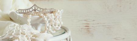 website banner achtergrond van witte parels halsketting en diamanten tiara op vintage tafel. gestemd beeld. selectieve aandacht Stockfoto