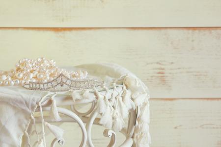 diamante: imagen del collar de perlas blanco y diadema de diamantes en la mesa de la vendimia. enfoque selectivo