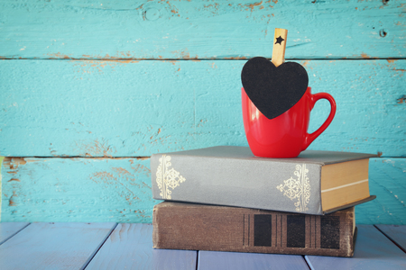 phrase novel: cup of coffee with a little heart shape chalkboard and to stack of old books.