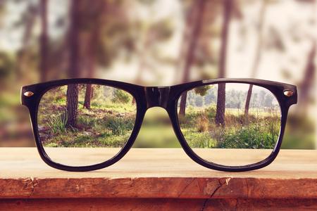 hipster okulary na drewnianym wiejskim stole naprzeciwko lasu. rocznik filtrowane