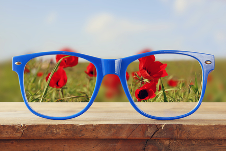 glasses eye: hipster glasses on a wooden rustic table in front of the field of red poppies. vintage filtered