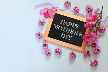 mothers day: flowers next to blackboard, on wooden table. happy mothers day concept Stock Photo