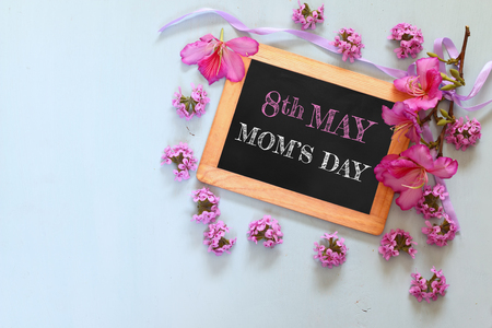 flowers next to blackboard, on wooden table. happy mother's day concept