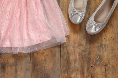 view an elegant wardrobe: vintage chiffon girls dress next to ballet shoes on wooden background. vintage filtered image