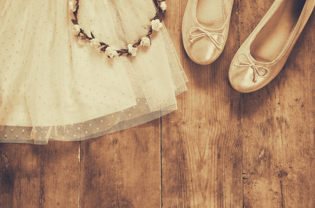 view an elegant wardrobe: vintage chiffon girls dress, floral tiara next to ballet shoes on wooden background. vintage filtered, sepia style image
