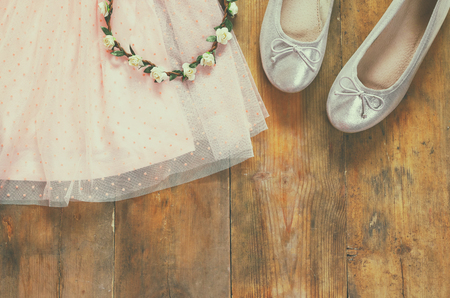 niños de compras: vintage chiffon girls dress, floral tiara next to ballet shoes on wooden background. vintage filtered image