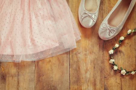 view an elegant wardrobe: vintage chiffon girls dress, floral tiara next to ballet shoes on wooden background. vintage filtered image