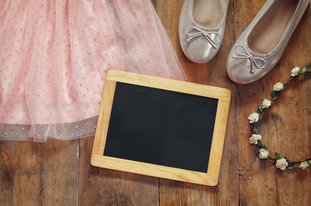 view an elegant wardrobe: vintage chiffon girls dress, floral tiara next to ballet shoes and blank blackboard on wooden background. vintage filtered image Stock Photo