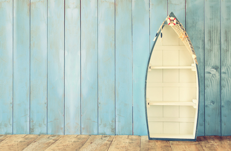 interior wallpaper: nautical boat shape shelves on wooden table. product display background, vintage filtered Stock Photo