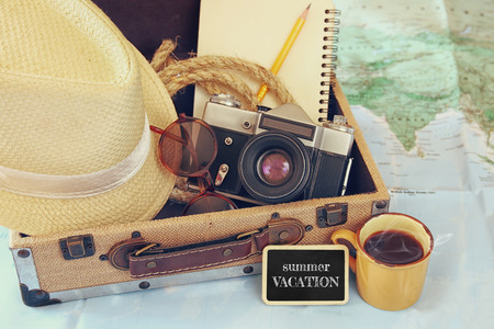 world travel: traveling concept. camera, cup of coffee, sunglasses, fedora hat and notebook. vintage filtered. selective focus Stock Photo