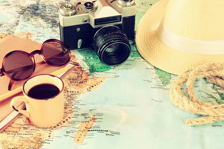 traveling concept. camera, cup of coffee, sunglasses, fedora hat and notebook. vintage filtered. selective focus Stock Photo