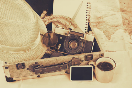traveling concept. camera, cup of coffee, sunglasses, fedora hat and notebook. sepia vintage style filtered. selective focus Stock Photo