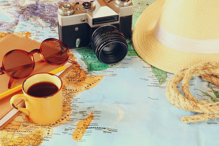 fedora: traveling concept. camera, cup of coffee, sunglasses, fedora hat and notebook. vintage filtered. selective focus Stock Photo