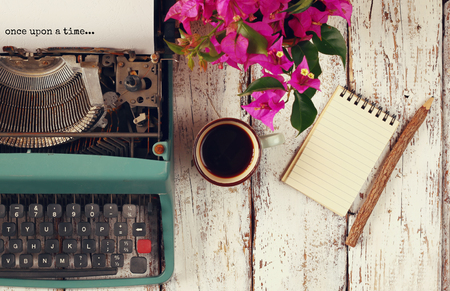 time: image of vintage typewriter with phrase once upon a time, blank notebook, cup of coffee on wooden table Stock Photo