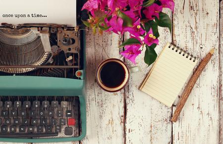 """Tiempo: imagen de la máquina de escribir de la vendimia con la frase """"érase una vez"""", cuaderno en blanco, una taza de café en la mesa de madera"""