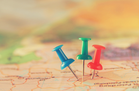 best travel destinations: pins attached to map, showing location or travel destination . retro style image. selective focus. Stock Photo