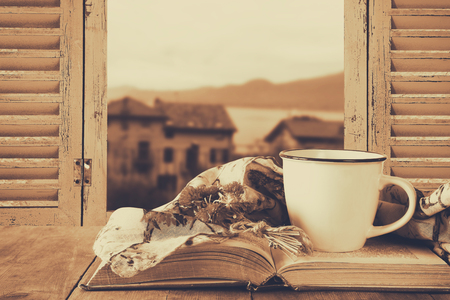 country house style: romantic scene of cup of coffee next to old book in front of countryside view outside of the old rustic window. filtered image