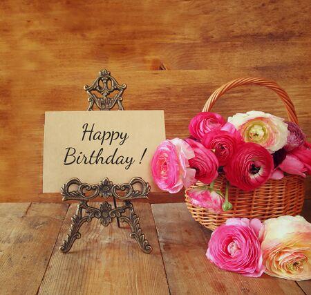 flores de cumpleaños: flores de color rosa en la cesta junto a la tarjeta con la frase feliz cumpleaños, sobre la mesa de madera
