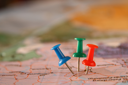 pins attached to map, showing location or travel destination . retro style image. selective focus. Archivio Fotografico
