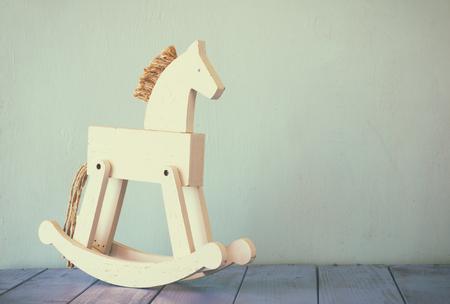 room decor: vintage rocking horse on wooden floor. retro filtered image.
