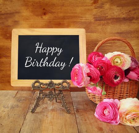 flores de cumpleaños: flores junto a la pizarra con la frase: feliz cumpleaños, sobre la mesa de madera