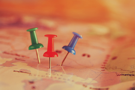 pinning: pins attached to map, showing location or travel destination . retro style image. selective focus. Stock Photo