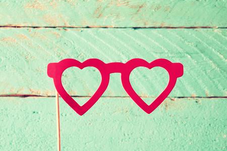 feminine background: paper heart shape fake glasses in sticks in front of wooden background. vintage filtered image Stock Photo