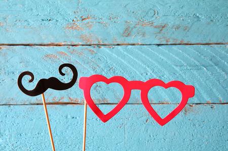 divercio n: gafas falsas la forma del corazón de papel y bigotes en palos delante de fondo de madera. imagen filtrada de la vendimia Foto de archivo