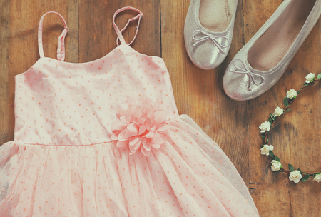 view an elegant wardrobe: vintage chiffon girls dress, floral tiara next to ballet shoes on wooden background. vintage filtered image