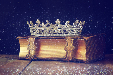 decorative crown on old book. vintage filtered. selective focus.