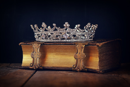 once: decorative crown on old book. vintage filtered. selective focus.