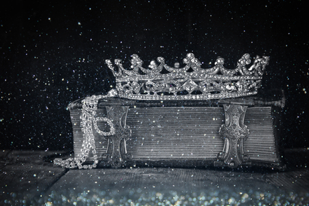 low key image of decorative crown on old book. black and white photo with flitter overlay. selective focus.